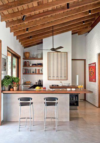 A bancada de cumaru divide a sala da pequena cozinha e atende também à mesa externa, ligada a este canto pela janela lateral. Ótima para refeições rápidas, sua base de alvenaria ainda armazena louças e utensílios.