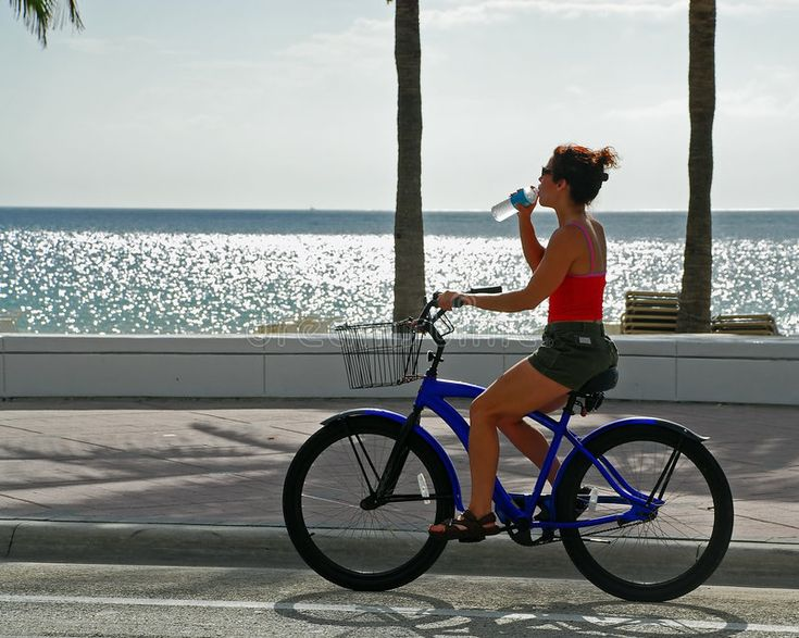 Girl on Bike Drinking Water. Young woman drinking water from a bottle while ridi…