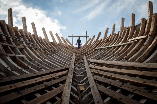 A Buginese man holds a hammer as he starting to work to install a wooden block in the hull of phinisi at Tanjung Bira Beach on May 2, 2014 in Bulukumba, South Sulawesi, Indonesia. Phinisi, a masterpiece of traditional Bugis-Makassar design, is a traditional wooden two-masted sailing ship, well-known as traditional sea transportation amongst the buginese people for many centuries.