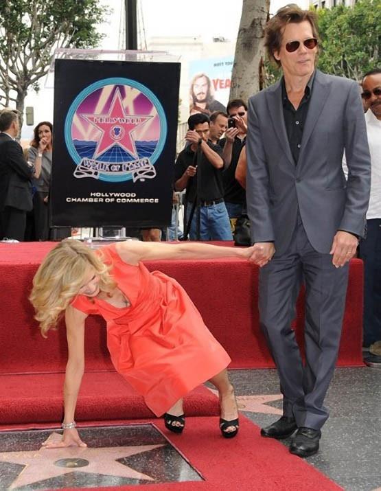 Кевин Бейкон старается не рассмеяться, пока павшая к его ногам Кира Седжвик поднимается на Аллее славы в Голливуде.