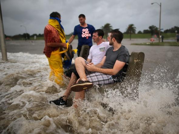 Um grupo de homens sentam-se em um banco na beira do lago Pontchartrain enquanto o furacão Isaac ainda se aproximava de Nova Orleans
