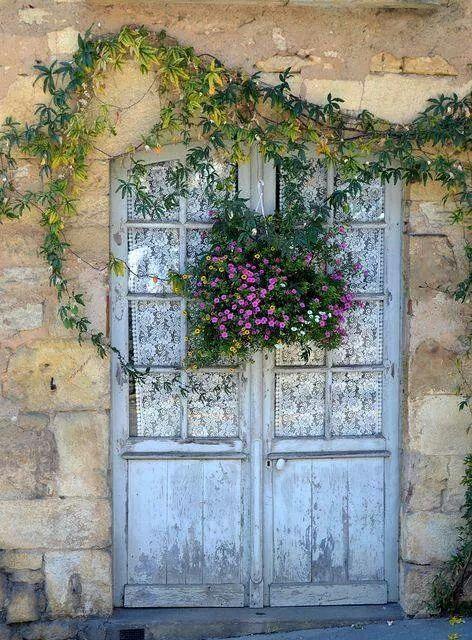 Vieille maison en pierre, portes françaises, rideaux de dentelle blanche et un pot de beaux bouquets suspendus pourpres