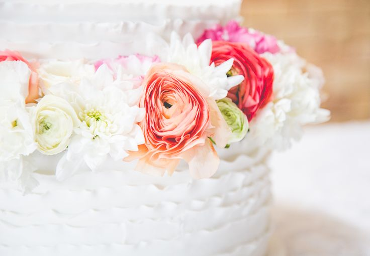 A white fondant ruffle wedding cake with fresh flowers including ranunculus, chrysanthemum, roses, lisianthus, and carnations at the ceremony for morning tea.