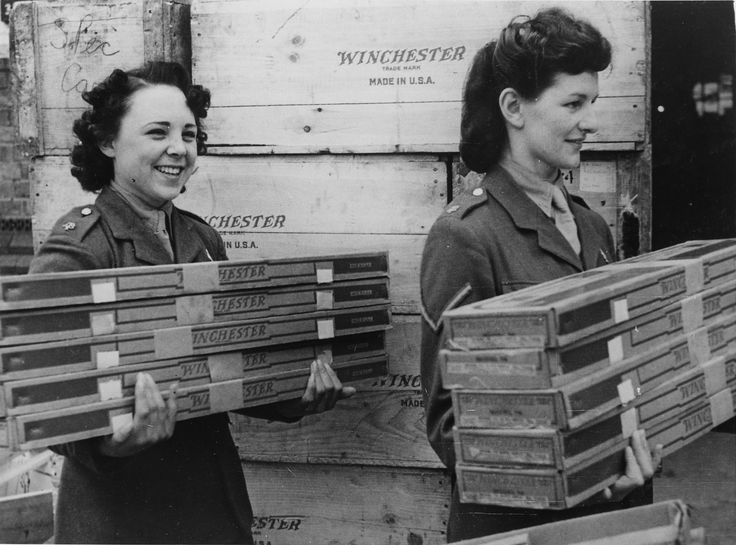 English girl members of the Auxiliary Territorial Service move armfuls of American rifles just arrived from US under lend lease. WWII