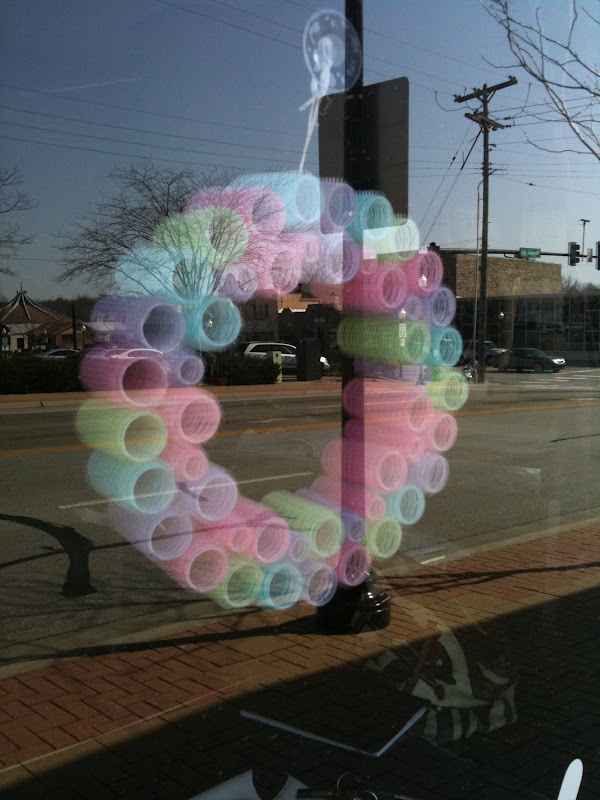 cute wreath made from old velcro hair rollers (in beauty shop window)//// Would you look at this ROE!!! I told you they were still good for something when you made me throw them out!!! LOLOLOLOL:)
