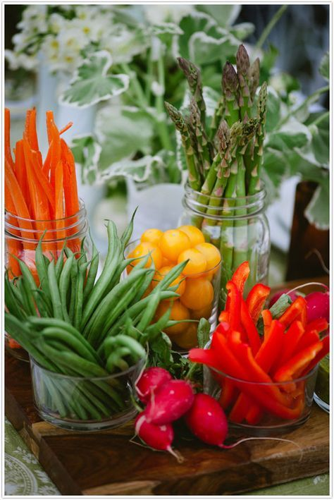 A beautiful vegetable crudite display, where carrots, peppers, asparagus, green beans and tomatoes are stood upright and ready for dipping