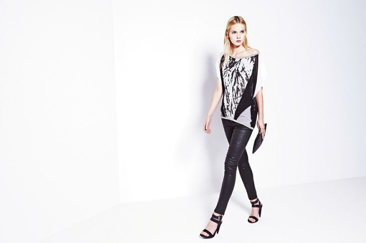 Czarne, dopasowane spodnie z woskowanej bawełny i jasny top z łączonych materiałów.