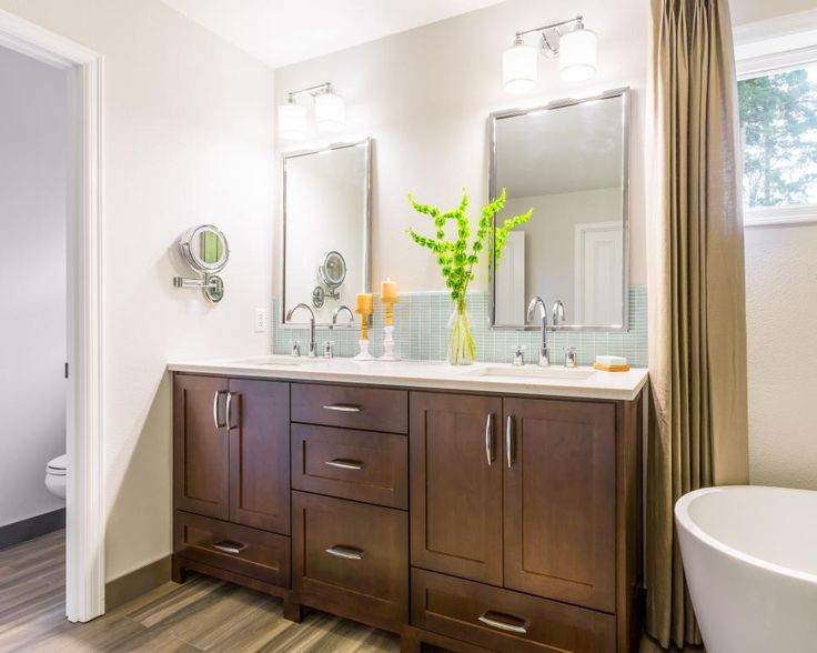 This master bathroom features a large double vanity and his and hers mirrors and lighting for a custom feel. A drawer at the bottom of the sink compartment provides additional storage that is typically unusable due to plumbing. A glass tile backsplash completes the space.
