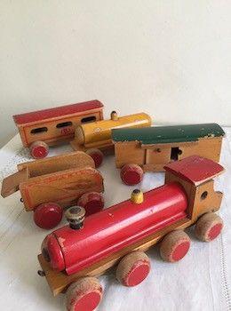 Ce petit train en bois des années 40 a déjà parcouru de nombreux kilomètres sur des rails imaginaires…. Il se compose d'une locomotive et de 4 wagons dont un wagon citerne. Il a gardé ses belles couleurs ….jaune, verte, rouge et saura faire le bonheur de petits ou des collectionneurs. Longueur totale : 1 mètre