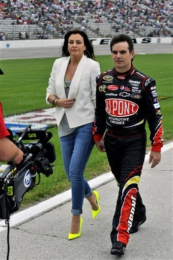 Jeff Gordon and his wife Ingrid Vandebosch walk down pit road during the NASCAR Sprint Cup Series auto race, Saturday, April 14, 2012, in Fort Worth, Texas.