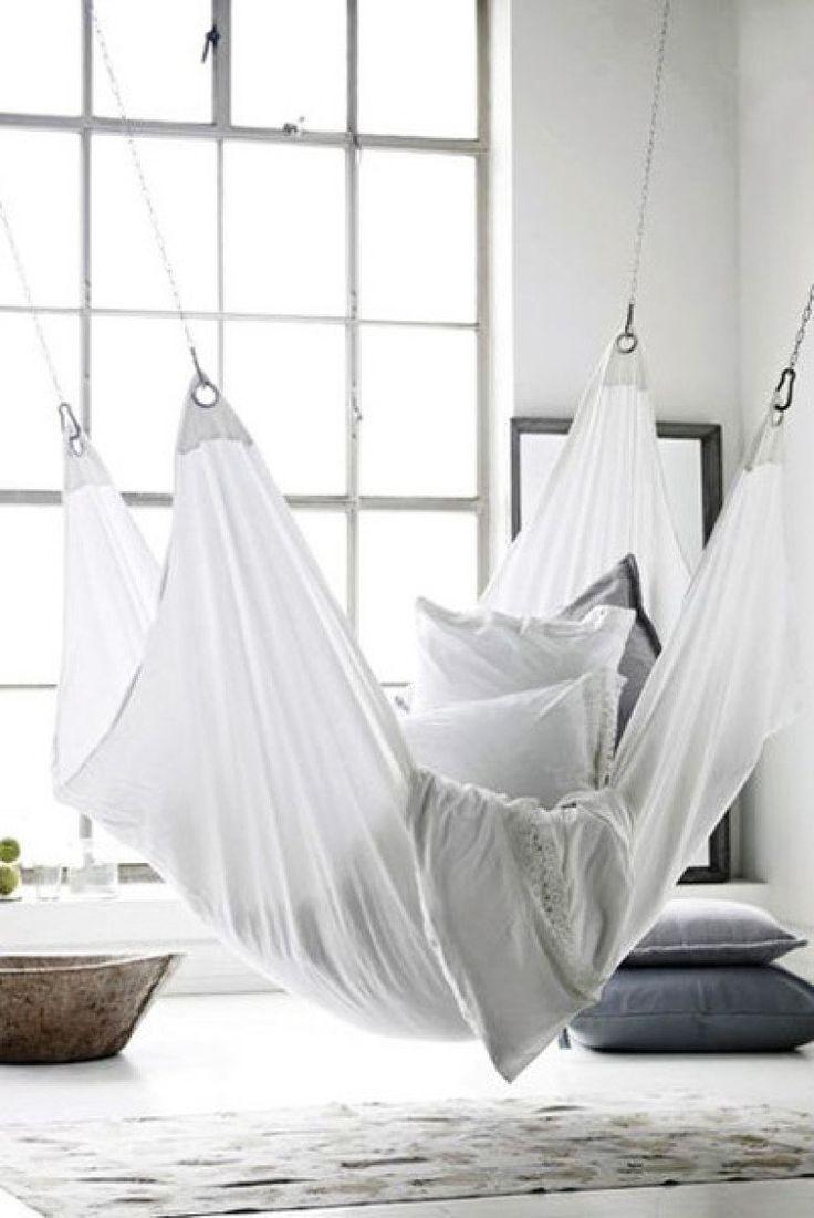 No ambiente cheio de luz natural com décor em tons de cinza e branco, a rede cheia de almofadas serve como refúgio.