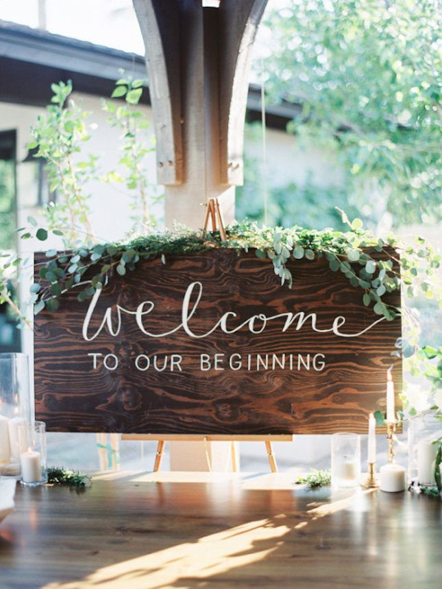 A wooden welcome sign surrounded by candlesticks and eucalyptus is the perfect way to greet guests at your earthy chic wedding.