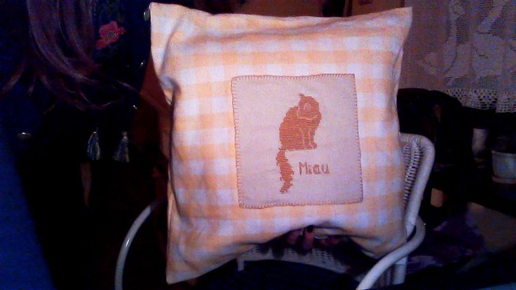 a lovely pillow with an embroided cat