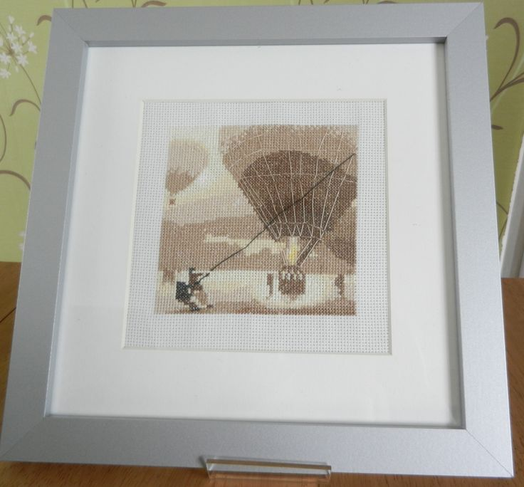 this wonderful design of a hot air balloon has been cross stitched and mounted into a silver frame by Tulipacious Designs.