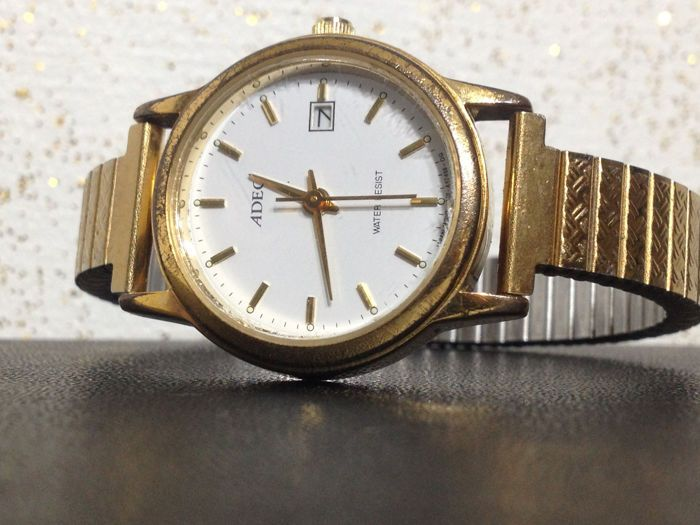 ADEC GN-4-S vrouwen horloge - geen minimumverkoopprijs  Elegante vrouw polshorloge van ADEC model: GN-4-SMet goudkleurige RVS behuizing en een armband met versieringen en logo quartz uurwerk ronde behuizing witte wijzerplaat met datum diafragmaBehuizing: goudkleurig staalTotaal gewicht: 314 gDe diameter van de behuizing: 27 mmBehuizing dikte: 7 mmArmband: Goudkleurig staalBreedte armband: 9 mmGesp: Stretch armbandUurwerk diameter: ca. 5 cmMovement: quartzMerk op: Lees zorgvuldigHet uurwerk…