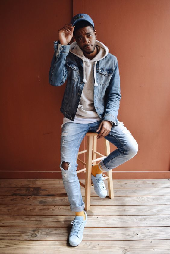 Busy days call for a simple yet stylish outfit, such as a blue denim jacket and light blue ripped jeans. Finish off this look with white leather low top sneakers.   Shop this look on Lookastic: https://lookastic.com/men/looks/denim-jacket-hoodie-crew-neck-t-shirt/18352   — Blue Baseball Cap  — Beige Hoodie  — Blue Denim Jacket  — White Crew-neck T-shirt  — Light Blue Ripped Jeans  — Yellow Socks  — White Leather Low Top Sneakers