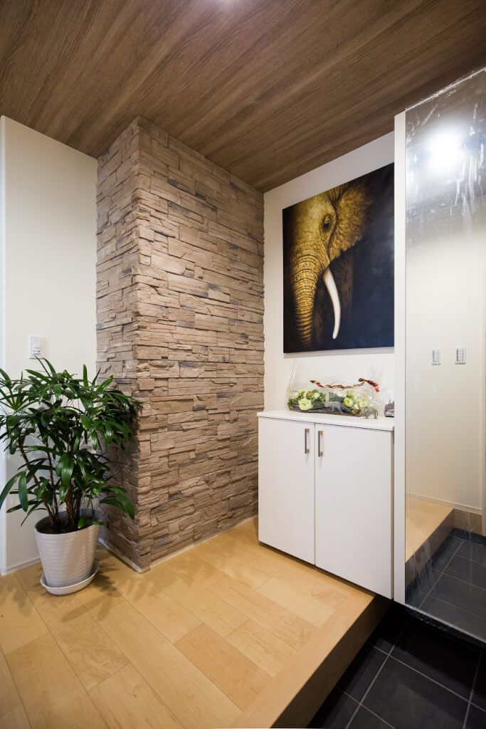 一角に貼られた擬石が印象的な玄関 ゴツゴツとしたワイルドな質感が 良い