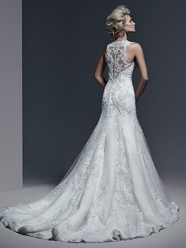 Bold lace appliqués; accented with sparkling Swarovski crystals; trail the length of this extravagant A-line wedding dress; complete with sweetheart neckline and dramatic illusion lace back. Finished with crystal button over zipper closure.