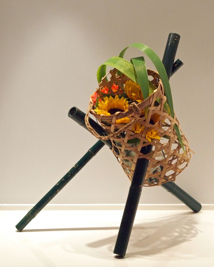 Modern basket ikebana. Bamboo sticks, Sun flowers, Gerbera, Gladiolus leaves.