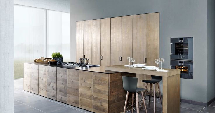 A kitchen with real metal and real oak wood.  Precious oak is crafted as a solid 3-layer wood to make the fronts of the kitchen block and refined in the elegant stain shade marsh oak. The warm bronze shade of the material used in the sliding folding doors Metal-X² – real metal filler applied by hand using a fine mesh structure – harmonises with the brown shades of the marsh oak.