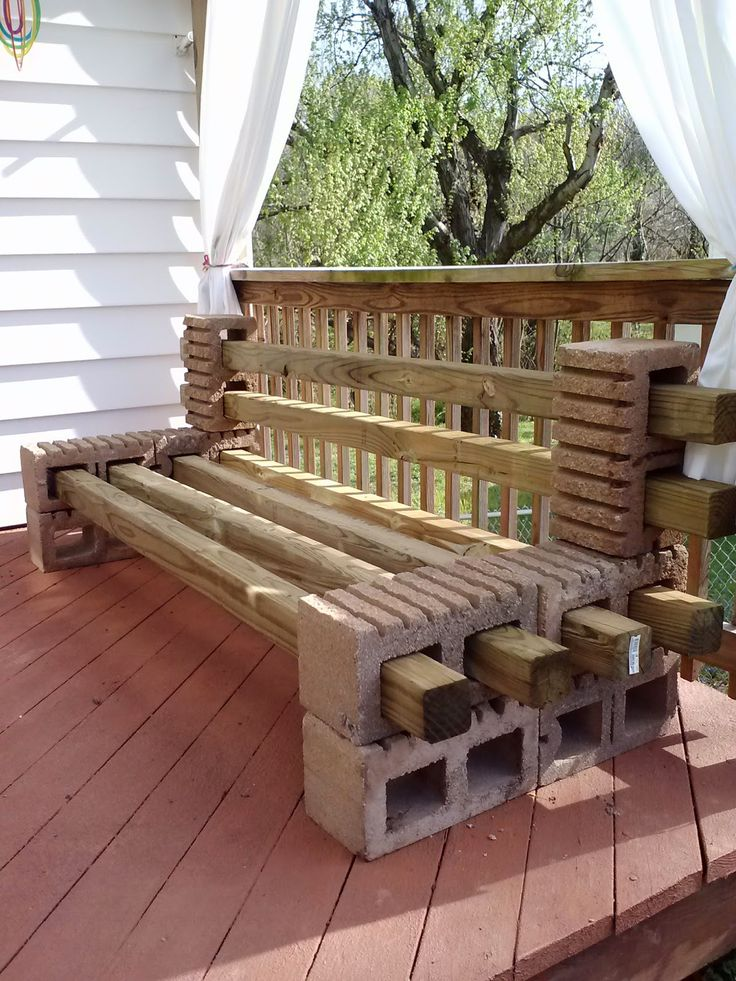 Spray paint the cinderblocks and wood dark brown, throw some patio pillows on there, and you have perfection