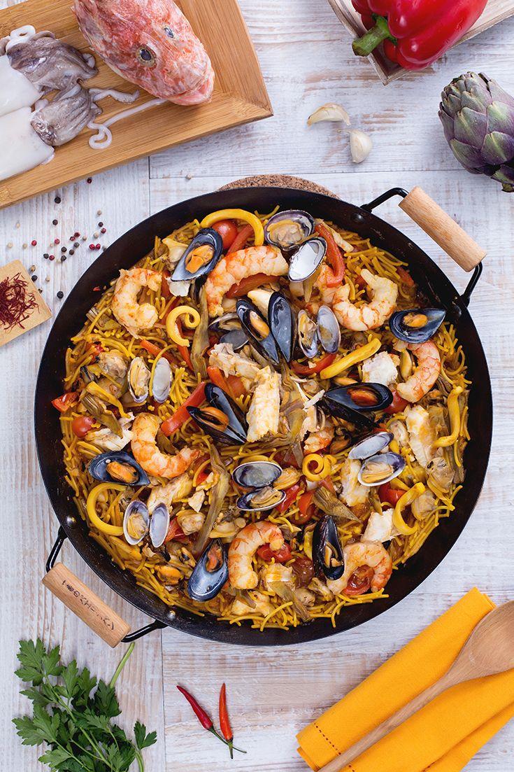 La #fideuà, anche se è cotta nella paella come l'omonima ricetta, è solo simile a questa! L'aggiunta di #pasta al ricchissimo condimento di #pesce, #crostacei e #molluschi rende questa pietanza completa, perfetta per una grande occasione di festa. La pasta è cotta come un risotto: non in acqua bollente ma da cruda assieme al resto grazie all'aggiunta di mestolate di #fumetto, così da amalgamare tutti i sapori! #ricetta #GialloZafferano #Valencia #Spanishrecipe #ExpoMilano2015