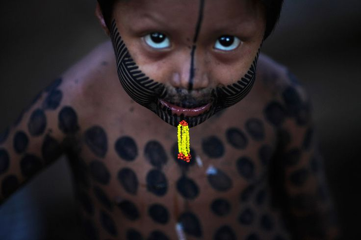Kayapo boy with traditional body paint and piercing
