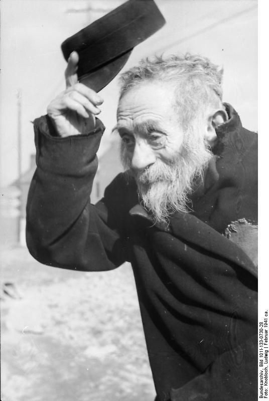 Old Jewish beggar in the streets of the Warsaw Ghetto, Feb 1941.