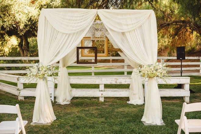 Softly draped, ceremony canopy with chandelier, picture frames, and white flowers.