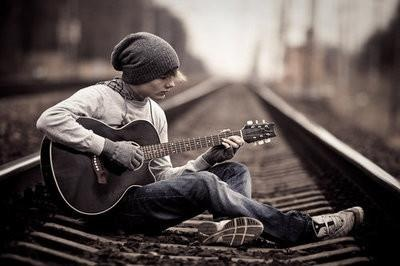 super adorable alternative boy with guitar, on the railway, with hat..