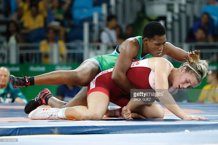 Hungary's Zsanett Nemeth (red) wrestles with Cameroon's Annabel Laure Ali in their women's 75kg freestyle repechage round 2 match on August 18, 2016, during the wrestling event of the Rio 2016 Olympic Games at the Carioca Arena 2 in Rio de Janeiro. / AFP / Jack GUEZ