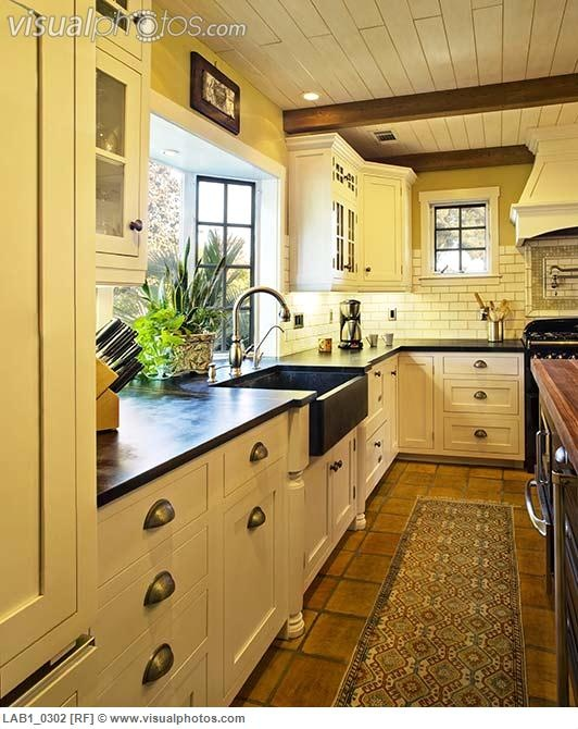 Country Kitchen With Flat Panel Cabinets Exposed Beam Bay Window European Terra Cotta Tile Flooring Subway