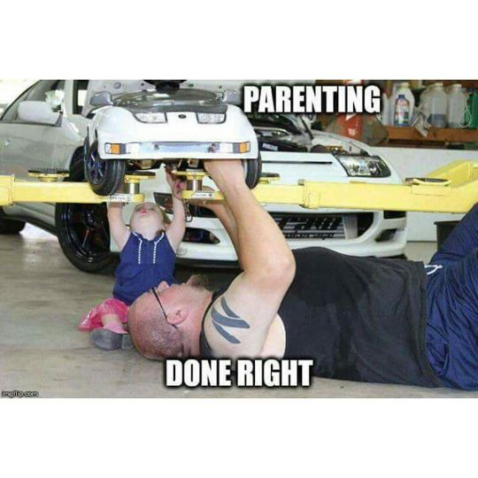 Typically a father would be helping his son fix a car but this father is helping his daughter on the car.