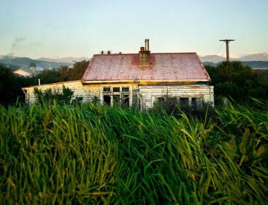 Old house with overgrown lawn, Hokitika, New Zealand