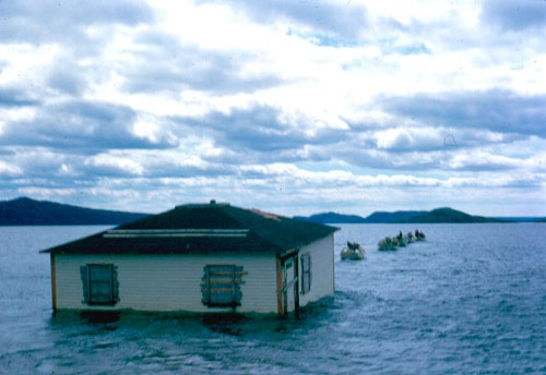 People moving a house across the sea, during resettlement of communities. Such communities as this were depopulated through resettlement programs of the provincial government between 1954 and 1975.Resettlement in Newfoundland terms was an organized approach to centralize the population into growth areas. Attempts of resettlement were thrust upon outport residents and whole communities between 1954 and 1975 which resulted in the abandonment of 300 communities and nearly 30,000 people moved.