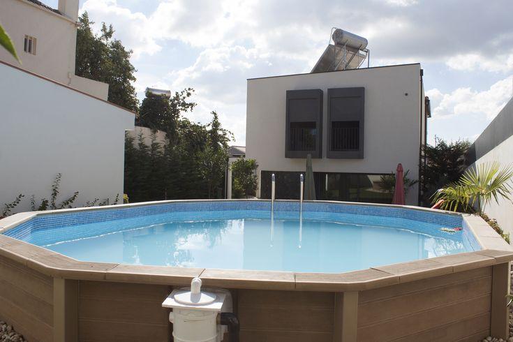 Piscina decagonal (Naturalis 01) em betão com estrutura exterior com aspeto de madeira.