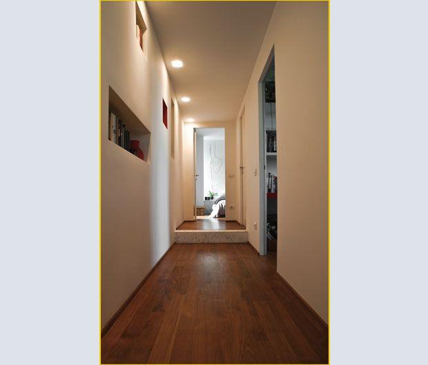 Collocata al termine del corridoio, la zona notte padronale, composta da camera, bagno e un piccolo disimpegno adibito a spogliatoio, occupa l'intera sezione dell'appartamento. La parete rossa è inter
