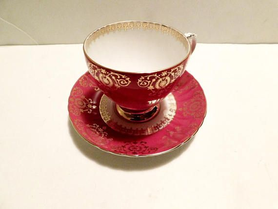 """Cup and saucer in pattern 9142 (7142?), a solid red with gold scroll pattern, gold accenting  The cup is 3 1/16"""" (7.8 cm) high x 3 7/16"""" (8.7 cm) at the brim and the saucer is 5 9/16"""" (14.1 cm) ) in diameter  This set is in very good condition and only appears to have seen use as a collectible  Made of fine bone china from England by Royal Grafton    This item has no nicks, chips, cracks, or signs of repair 