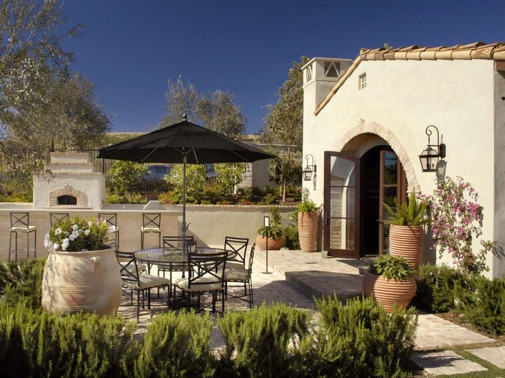 This enchanting Southwestern patio is outfitted with a glass-top dining table and patio umbrella. Low-maintenance container gardens add color and dimension to the outdoor entertaining space. An outdoor fireplace echoes the Spanish-style features of the adobe home.