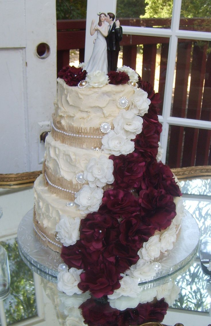 ivory textured wedding cake with burlap ribbon and flower make this a country chic wedding cake.