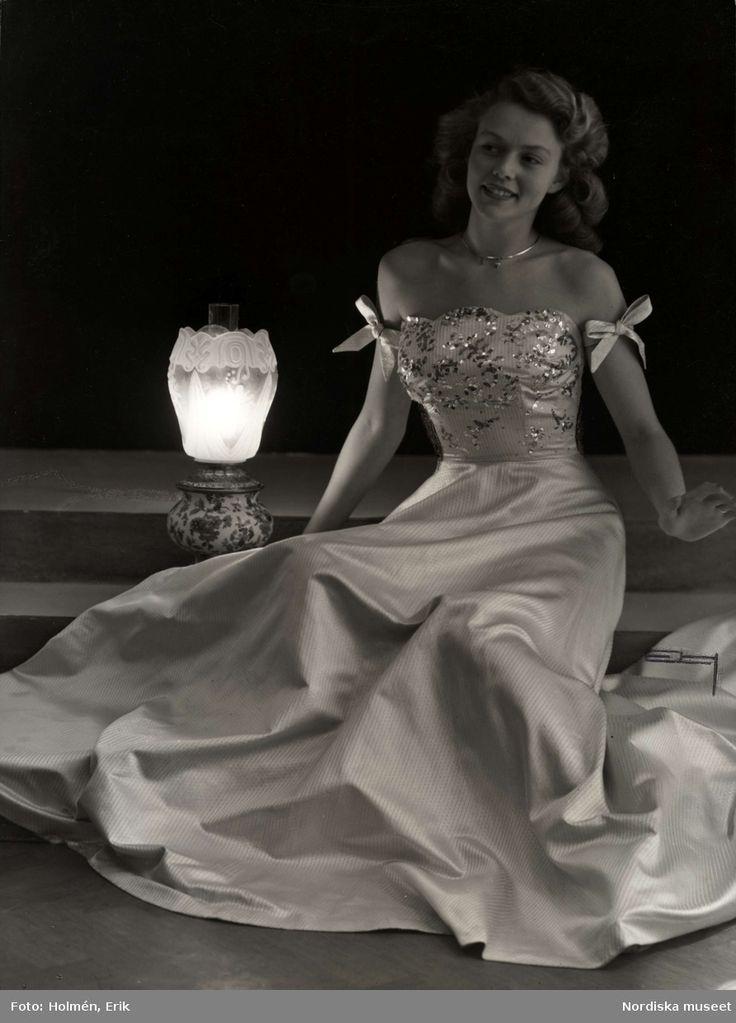 Klänningar på NK, november 1946. Modell i lång, ärmlös aftonklänning med mestallbroderier sitter i trappa med lampa bredvid sig. Foto: Erik Holmén för Nordiska Kompaniet