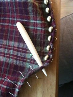 Attaching shanked buttons on medieval clothing