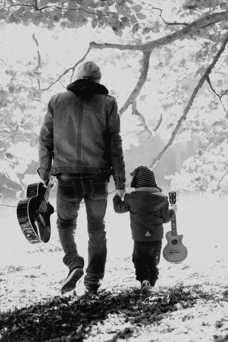 papá caminando con su hijo y una guitarra en la mano