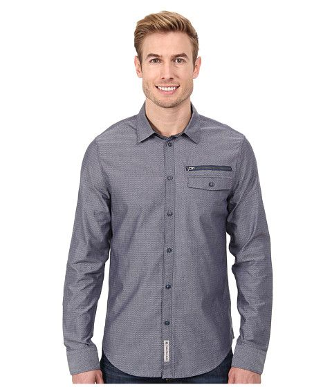 A micro geometric pattern decorates the finely woven cotton shirt.
