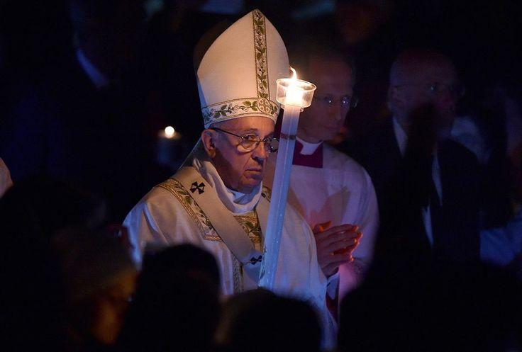 Paavi Franciscus pitelee kynttilää pääsiäismessussa.