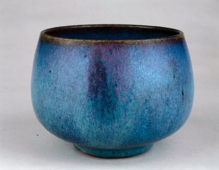 Guangdong stoneware deep bowl. Dark grey body covered in thick sky-blue glaze suffused with purple. Base glazed and foot rim unglazed. Body reddish where exposed. Qing dynasty. The British Museum.