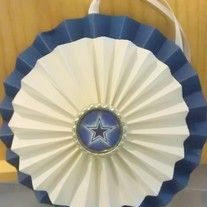"A handmade double paper rosette hanging. Bottom rosette is 5"" and top is 4"". Has a flattened bottlecap in middle of designated team. Rosettes are made from decorative paper, cardstock, heavy paper, etc... to depict team colors.   Can be used as a birthday decoration/gift or other gift, not just..."