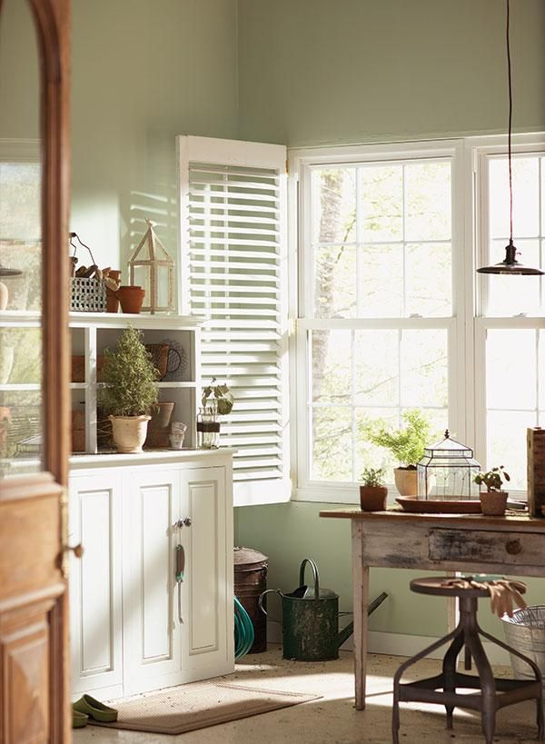 Behr's Topiary Tint feels fresh and bright in this mudroom. We love the way it picks up on the soft greenery outside the window! #paint