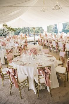 Pink and white wedding reception under a tent with hanging lamps decor | Una recepción en blanco y rosa con una carpa de tela y lámparas de araña colgantes.