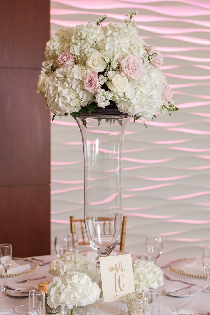 White and Gold Wedding Reception with Tall White Hydrangea, Rose, and Blush Pink Rose Centerpiece in Glass Vase, and Stylish Gold Printed Table Number on Square White Paper